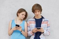 Två tonåringar som använder moderna grejer som spelar spelar online-, medan stå mot den gråa betongväggen Nätt flicka i blåttklän arkivbilder