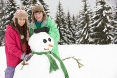 Två tonåringar som bygger snowmanen skidar på, ferie Royaltyfria Bilder