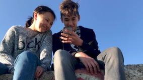 Två tonåringar som sitter i gatan och de hållande ögonen på roliga videona på telefonen arkivfilmer