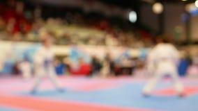 Två tonåringar som slåss på den suddiga karatemästerskapet - lager videofilmer