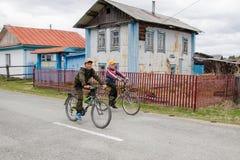 Två tonåringar springer på cyklar till och med byn förbi det gamla huset royaltyfri foto