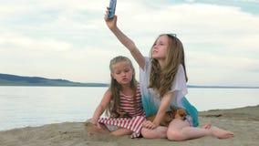 Två tonårs- barn sitter på stranden i telefon
