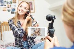 Två tonårs- flickor som antecknar skönhetbloggen i sovrum Arkivfoton