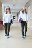 Två tonårs- flickor som går i böcker för text för lång skolakorridor bärande Fotografering för Bildbyråer