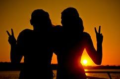 Två tonårs- flickor som ger fredtecknet på solnedgången arkivbilder