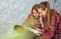 Två tonårs- flickor som läser modetidskriften som hemma sitter på en soffa fotografering för bildbyråer