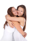 Två tonårs- flickor som ler och kramar Arkivbild