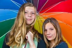 Två tonårs- flickor under det färgrika paraplyet Royaltyfri Foto
