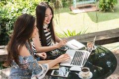 Två tonårs- kvinnor möter i coffee shopbruksbärbar dator tillsammans in aft arkivbilder