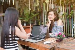 Två tonårs- kvinnor möter i coffee shopbruksbärbar dator tillsammans in aft royaltyfri bild