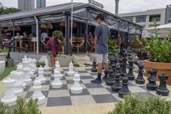 Två tonårs- pojkar som spelar utomhus- schack fotografering för bildbyråer