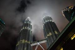 Två torn som petar till och med den disiga natthimlen royaltyfri foto