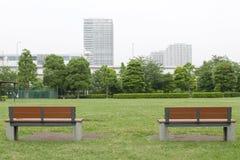 Två träbänkar och gräsgolv parkerar offentligt Arkivbilder