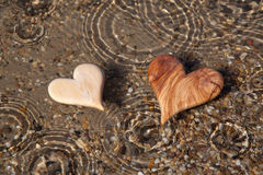Två trähjärtor formar i naturen för hälsningkort. arkivfoto