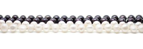 Två trådar av vita och svarta pärlor som flätas samman på vit bakgrund royaltyfri foto