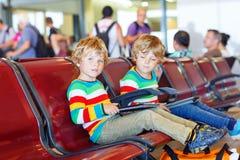 Två tröttade små siblingpojkar på flygplatsen Arkivbild