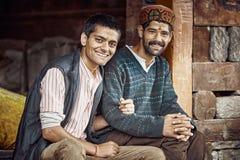 Två traditionella indiska män sitter nära huset, leende på kameran Arkivfoto