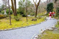 Två traditionella japanska flickor går till och med trädgården Royaltyfria Foton