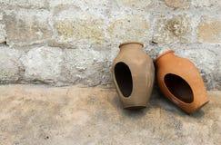Två traditionella stora lerakrus till lagringsvatten som överges i gatan arkivfoto