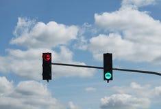 Två trafikljus en som är röda till vänstra sidan och en klartecken till körning som är framåt eller som är höger med en molnig hi arkivbilder