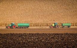 Två traktorer är klara att ta den bort skörden av havre på höstfält Royaltyfria Bilder