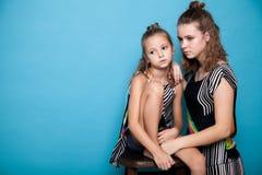 Två trendiga flickor som poserar med en kamera på en blå bakgrund Royaltyfri Foto