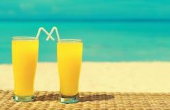 Två tropiska nya fruktsafter på den tropiska stranden Ferie och vacatio Royaltyfri Bild