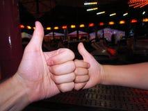 Två tummar upp av en liten och vuxen hand som arkivfoton