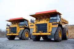 Två tunga lastbilar för vagnen av gods i ett villebråd Arkivbild