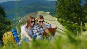 Två turister använder bärbara datorer i campa Mot bakgrunden av de pittoreska bergen Royaltyfri Foto