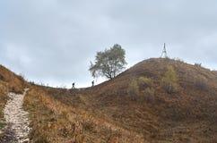 Två turister klättrar banan till överkanten av berget Arkivbilder