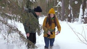 Två turister med ryggsäckar, en ung man och en flicka, i en vinter snö-täckt skogblick på en pappers- översikt lager videofilmer