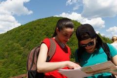 Två turister med ryggsäckar som ser en pappers- översikt Royaltyfri Bild