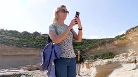 Två turister promenerar den steniga kusten av havet bland enorma bruna stenar, lera på en blåsig solig dag Därefter lager videofilmer