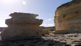 Två turister promenerar den steniga kusten av havet bland enorma bruna stenar, lera på en blåsig solig dag familj lager videofilmer