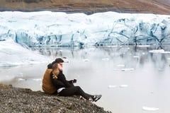 Två turister sitter nära glaciärisberget i Island arkivfoton