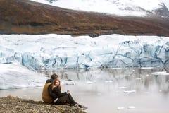 Två turister sitter nära glaciärisberget i Island arkivfoto