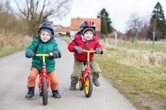 Två tvilling- litet barnpojkar som har gyckel på cyklar Arkivfoton
