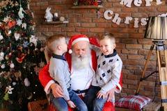 Två tvilling- pojkar gör växelvis önska i öra av Santa Claus i de Royaltyfri Bild