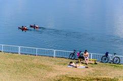 Två two-seaterkanoter i vatten och två personer på stranden royaltyfri fotografi