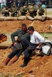 Två tyska soldater-reenactor sitter på jordningen och talar Arkivbild