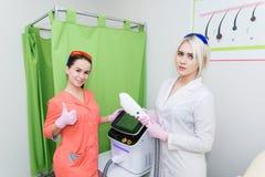Två ung flickacosmetologists för hårborttagning står bredvid maskinen och showen a för laser-hårborttagning som Flickor visar a royaltyfria foton