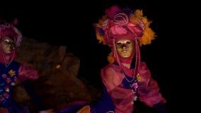 Två ung flickadansare i ljusa dräkter med blommor och guld- maskeringar dansar vinka deras händer de dansar på natten arkivfilmer