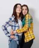 Två ung flickasystrar eller vänner kram och leende som ser ramen arkivbild