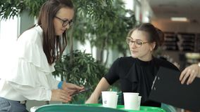 Två unga affärsflickor sitter på en tabell i ett kafé med kaffe och diskuterar arbetet Kaffe lunch, lunch, arbete arkivfilmer