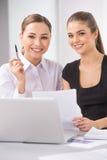 Två unga affärskvinna eller kontorsarbetare som diskuterar skrivbordsarbete Royaltyfri Foto