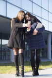 Två unga affärskvinnor fotograferade mobiltelefonen Fotografering för Bildbyråer
