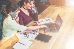 Två unga affärskvinnor sitter på tabellen, talar på mobiltelefonen och använder bärbara datorn Arkivfoto