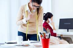 Två unga affärskvinnor som arbetar i hennes kontor Arkivfoto