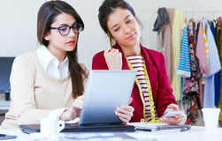Två unga affärskvinnor som arbetar med den digitala minnestavlan i henne som är offic Arkivbild